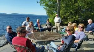 dozen folks by teh lake at table  nice!